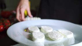 Putting mozzarella slices on the plate, cooking Caprese salad. Part of the set stock footage