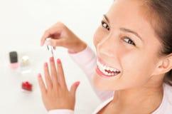 Putting nail polish - beauty fun. Nail polish woman having fun at spa. Cute asian caucasian girl on white background Stock Photography