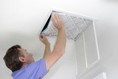 Putting In a New Air Filter. Guy placing into a square ceiling intake vent a clean white and blue air filter. As regular monthly maintenance a male puts in a new royalty free stock photo