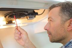 Putting in new extractor fan Stock Photo