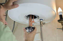 Putting a new water heater. Man`s hand putting a new water heater in a boiler royalty free stock images