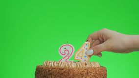 Putting a number twenty four birthday candle on a delicious cake, green screen 24