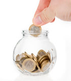 Putting one euro coin into jar. Hand putting one euro coin into money jar isolated on white Stock Image