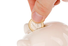 Putting one euro coin into piggy bank. Hand putting one euro coin into piggy bank isolated on white Royalty Free Stock Images