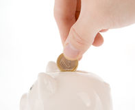 Putting one euro coin into piggy bank. Hand putting one euro coin into piggy bank isolated on white Stock Photography