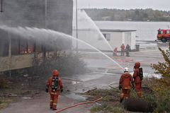 Putting out the fire. Firemen hosing down a burning building Stock Photos