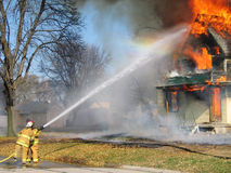 Putting Out The Flames. This was a controled house fire in Snyder, NE. I was there to capture a few shots just in the knick of time. The sun was hsining just stock photos