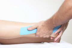 Putting a physio tape on a leg Stock Images
