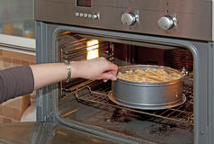 Putting a pie in the oven. Woman putting an apple pie in the oven Stock Image
