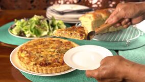 Putting a piece of green pea and bacon quiche into a white ceramic dish.