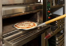 Putting pizza in oven Royalty Free Stock Image