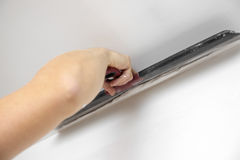 Putting plaster on the wall with spatula stock image