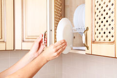 Putting plate in the closet. Stock Photography