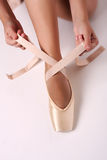 Putting on pointe ballet shoes stock images