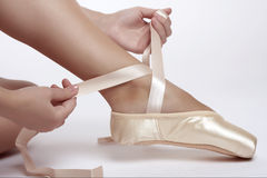 Putting on pointe ballet shoes. Sitting girl puts her pointe ballet shoes Stock Photography