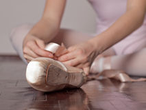 Putting on pointe ballet shoes royalty free stock images