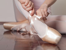 Putting on pointe ballet shoes Royalty Free Stock Photo