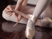 Putting on pointe ballet shoes Stock Photos
