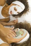 Putting puryfing mask. Happy young women lying on towel and putting face mask Royalty Free Stock Image