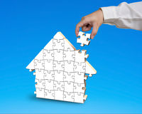 Putting puzzle in house shape Stock Photography
