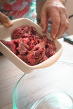 Putting raw meat in the baking dish vertical Royalty Free Stock Images