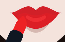 Putting red lipstick on lips Royalty Free Stock Photography