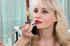 Putting red lipstick. Makeup artist putting red lipstick on attractive woman lips in salon Royalty Free Stock Photography