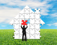 Putting red puzzle into house shape Stock Image