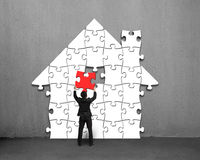 Putting red puzzle into house shape on wall Royalty Free Stock Photos