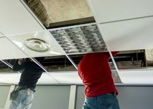Putting or repairing up a suspended ceiling. Builder putting or repairing up a suspended ceiling Royalty Free Stock Image