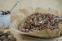 Putting roasted walnuts on cake with a spoon Royalty Free Stock Images