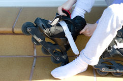 Putting on roller blades. Child sitting on step Putting on roller blades Stock Photos