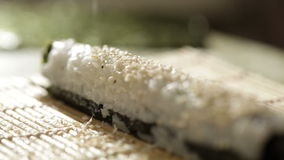 Putting sesame on sushi roll. Royalty Free Stock Photo