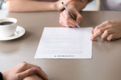Putting signature on contract, family mortgage, health insurance. Man signing loan contract for family needs, health insurance for young families, couple agreed Royalty Free Stock Photos