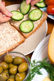 Putting slices of cucumber on tuna sandwich Royalty Free Stock Photo