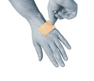 Putting a small adhesive, bandage on a arm Stock Photos