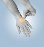 Putting a small adhesive, bandage on a arm. Putting a small adhesive, bandage on arm Stock Image