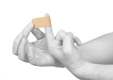 Putting a small adhesive plaster on a finger. Royalty Free Stock Image