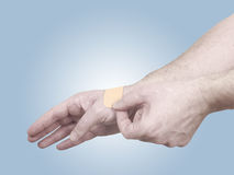 Putting a small adhesive plaster on a palm. Stock Photography