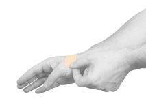Putting a small adhesive plaster on a palm. Royalty Free Stock Image