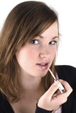 Putting on some lipgloss. Beautiful teenage girl is putting up lipgloss, isolated on a white background stock photography