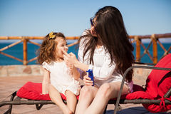 Putting some sunblock on. Young women putting some sunblock on her daughter's face before going down to the beach on a sunny day Royalty Free Stock Image