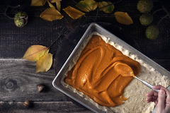 Putting spicy pumpkin puree on the dough for pumpkin pie top view Royalty Free Stock Photo