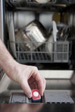 Putting tab into dishwasher Royalty Free Stock Photo