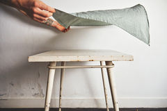 Putting tablecloth on old white table Stock Photos