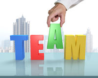 Putting A in for TEAM on glass table Royalty Free Stock Photo