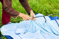 Putting up tent in a camping. Man putting up a tent in a camping stock photo