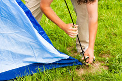 Putting up tent in a camping Royalty Free Stock Image