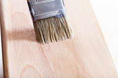 Putting varnish on beach wooden board. Putting layer of clear varnish on beach wooden board by paint brush Stock Photo