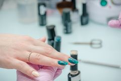 Putting varnish on nails. Processing of nails in beauty shop. Royalty Free Stock Images